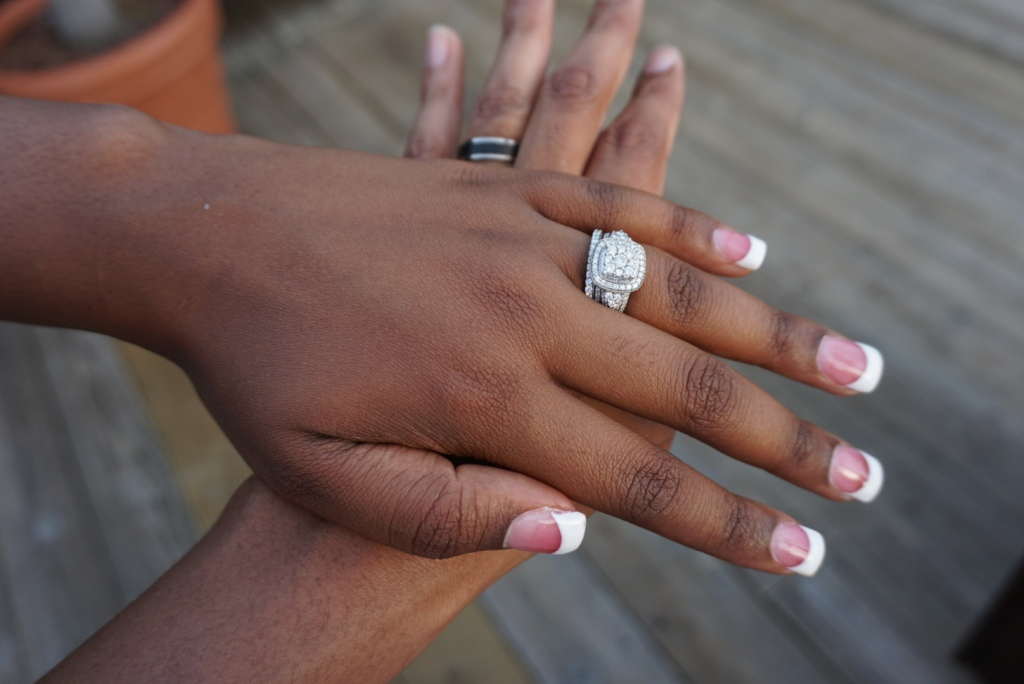 DC EASY's hand is stacked under his wife's hand as they each wear their wedding rings